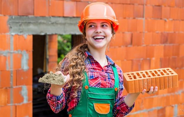 Oude bakstenen muur repareren. kind draagt helm op bouwplaats. tienermeisje bouwer met bouwsteen. metselaar kind bij het repareren van werk. concept van renovatie in werkplaats. drukke professionele timmerman.