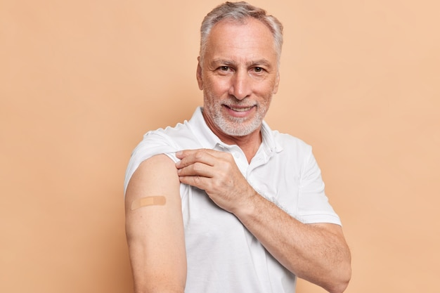 Oude bebaarde man is ingeënt tegen coronavirus toont armen met hechtpleister geeft om gezond tijdens pandemische poses tegen bruine muur