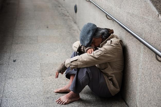 Oude bedelaar of dakloze vuile man zonder schoenen die en op gang zitten slapen
