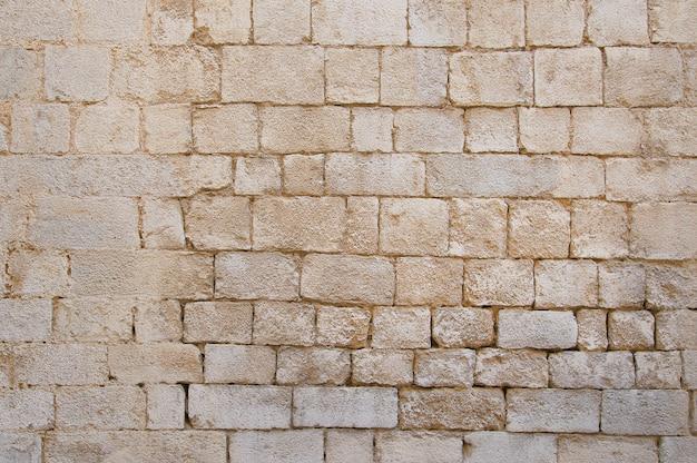 Oude beige stenen muur achtergrond