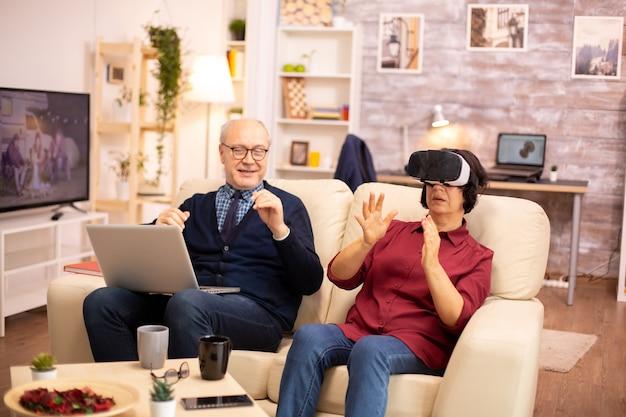 Oude bejaarde gepensioneerde vrouw van in de zestig die voor het eerst virtual reality ervaart in hun gezellige appartement