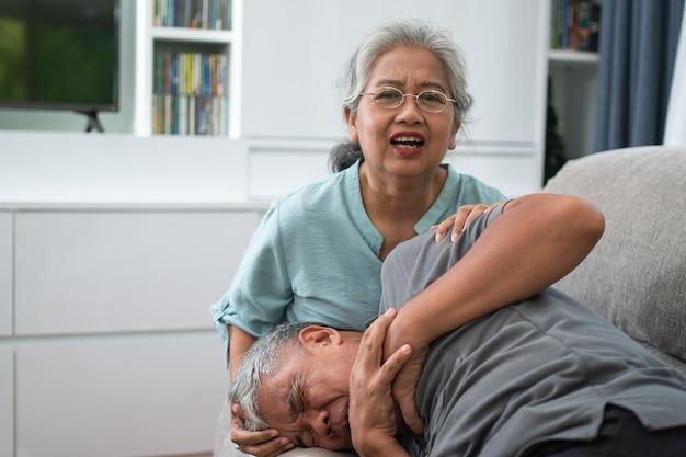 Oude bejaarde man heeft pijn met zijn handen op zijn borst en zijn vrouw roept om hulp