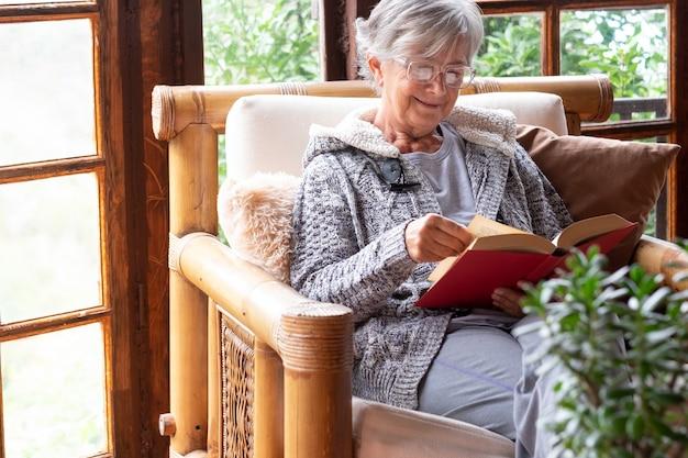 Oude bejaarde vrouw die thuis op een leunstoel zit en een boek leest met een warme trui en een bril. comfortabele woonkamer, houten raam