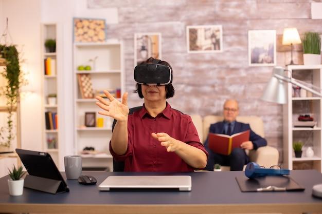 Oude bejaarde vrouw gebruikt voor het eerst een vr virtual reality-headset in haar huis. concept van actieve ouderen die moderne technologie gebruiken
