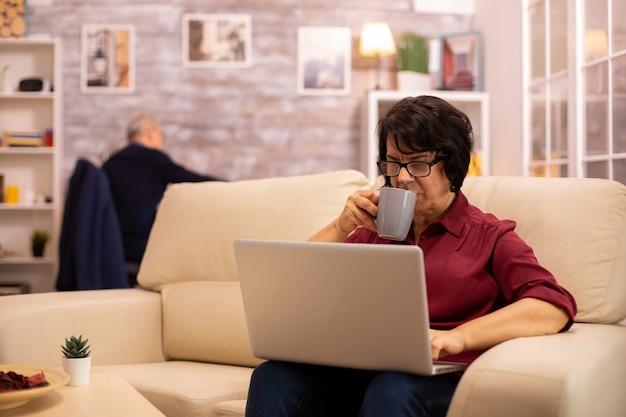 Oude bejaarde vrouw op haar bank werkt aan een moderne laptop in haar gezellige woonkamer. haar man is op de achtergrond