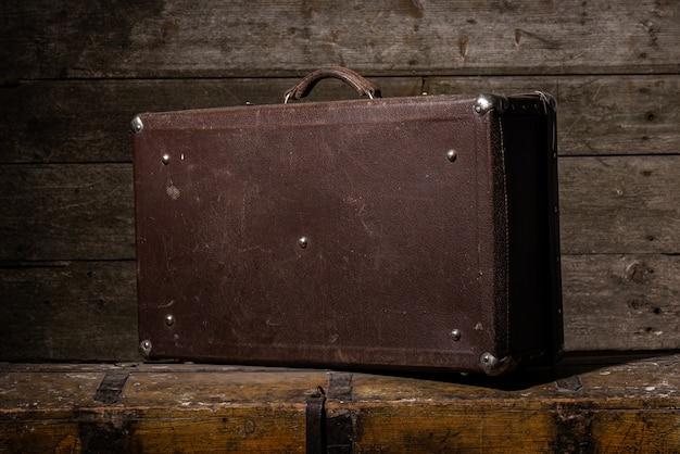 Oude bekraste koffer staat op de houten tafel