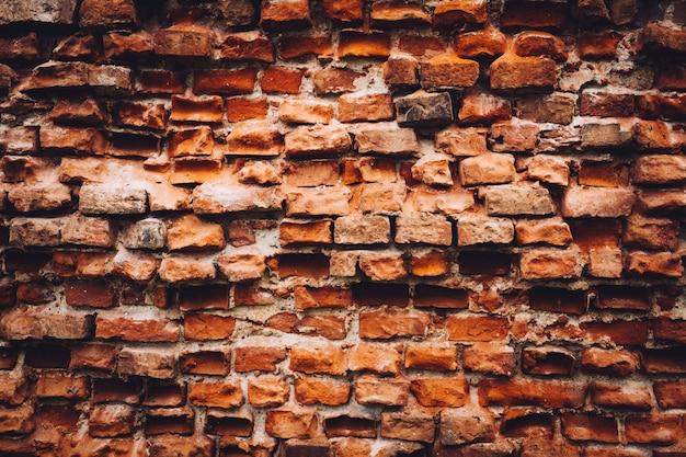 Oude beschadigde muur gemaakt van rode bakstenen.