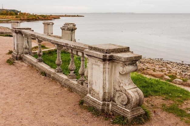 Oude betonnen reling tegen de zee.