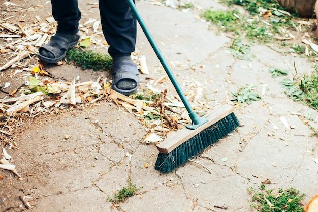 Oude bezem en metalen lepel met afval in de handen van mannen van werkhandschoenen