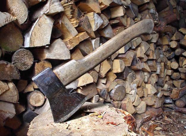 Oude bijl op een brandhoutachtergrond