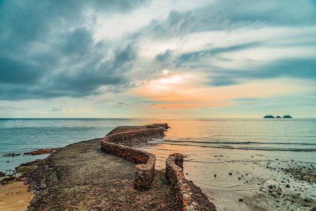 Oude birke-rotspier dichtbij kustlijn bij zonsondergang.