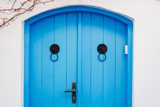 Oude blauwe deur met ringen op een witte muur van het huis