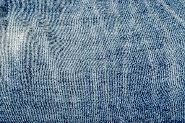 Oude blauwe jeans textuur achtergrond close-up. denimstofpatroon, ruw katoenen doekbehang met exemplaarruimte