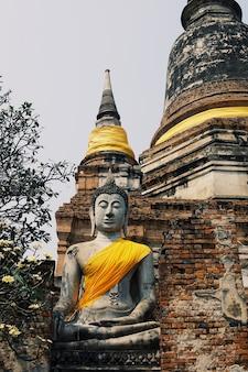 Oude boeddhabeelden die op bakstenen muren in thaise tempels worden geplaatst.