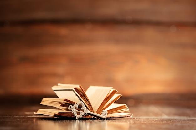 Oude boek en sleutel op houten tafel