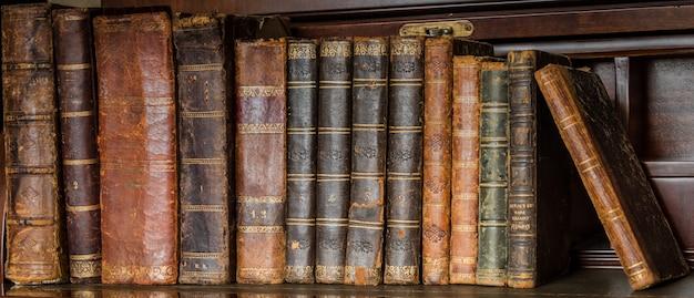 Oude boeken die op houten plank worden geplaatst
