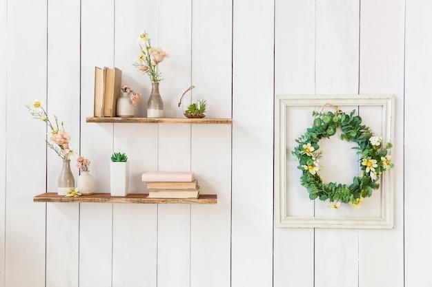Oude boeken en bloemen in een vaas op een houten plankframe met bloemen op een houten muur w