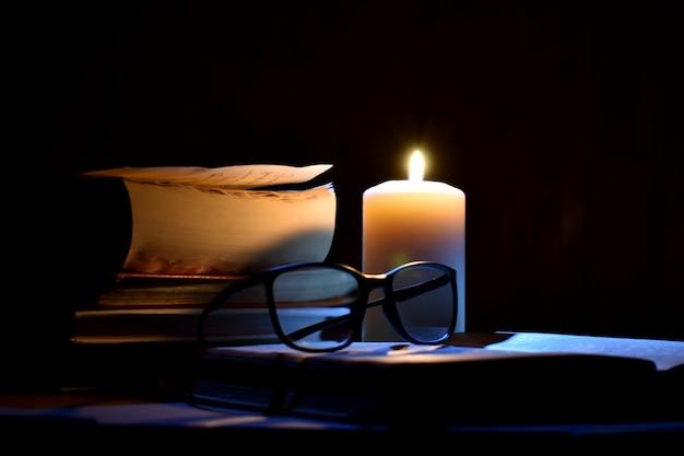Oude boeken en brandende kaarsen op een zwarte achtergrond. oude manuscripten bij kaarslicht.