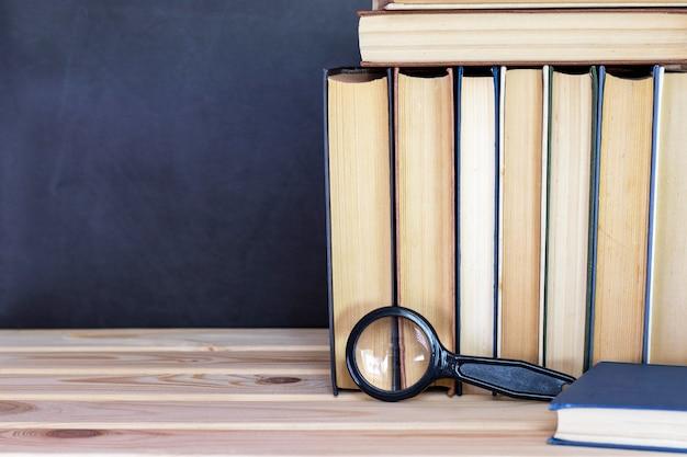Oude boeken en vergrootglas op houten plank op donker