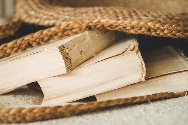 Oude boeken en vintage strozak op witte warme deken. tas stro zomer vrouw. bruine handgemaakte natuurtas.