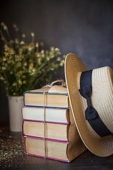 Oude boeken in een stapel verpakt in inpakpapier en een strooien hoed op een houten tafel. donkere sleutel.