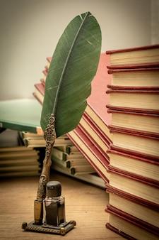 Oude boeken in wanorde gestapeld een oude pen met zijn inkt en een notitieblok op een oude houten tafel