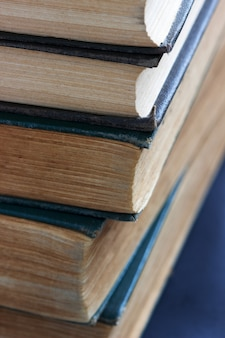 Oude boeken met gerafelde covers op een donkere tafel.