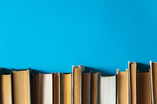 Oude boeken op een plank met blauwe achtergrond