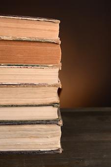 Oude boeken op tafel op bruine achtergrond