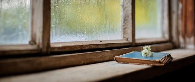 Oude boeken op van het dorps houten natte venster, copyspace.