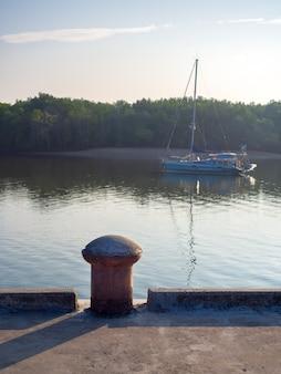 Oude bolder zonder meertouw op betonnen haven op rivieroever met jacht op de zee op mangrovebos