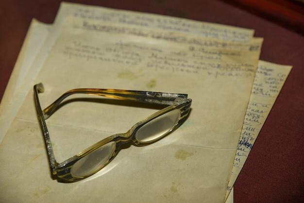 Oude bril op geel briefpapier, retro.
