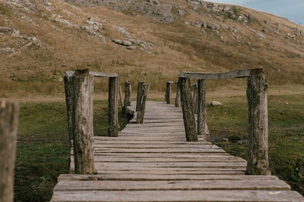 Oude brug van planken in een veld