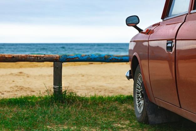 Oude bruine auto op het zandstrand met een blauwe logboekomheining, zomervakantie aan zee.