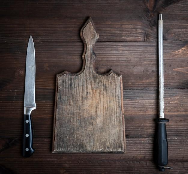 Oude bruine houten snijplank en mes met verscherping