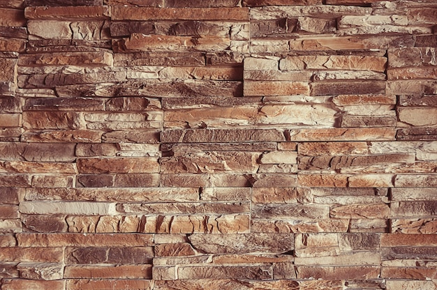 Oude bruine van de steenmuur textuur als achtergrond