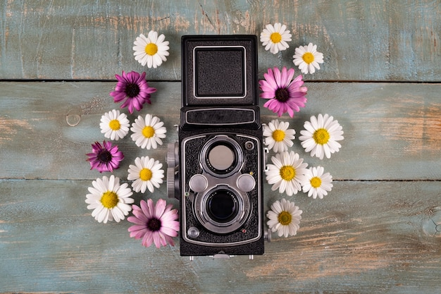 Oude camera met bloemen op blauwe houten achtergrond