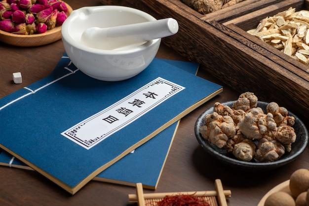 Oude chinese geneeskundeboeken en kruiden op tafel.