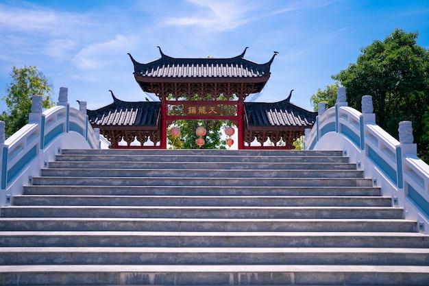Oude chinese stijl toegangsdeur met kromme trap brug met blauwe lucht in the celestial dragon village, openbare reisbestemming in suphan buri, thailand