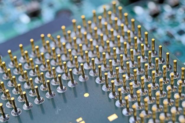 Oude computerprocessor met vergulde pootjes, microschakelingen erop, supermacrofoto