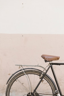 Oude cyclus die dichtbij concrete muur wordt geparkeerd