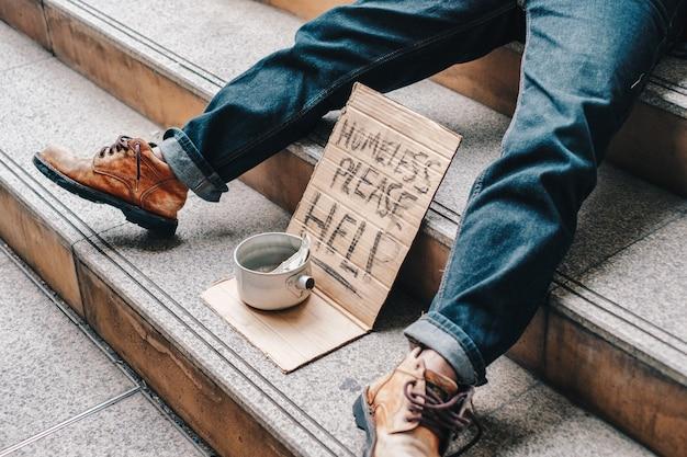 Oude dakloze die op trappen slaapt met karton en tekst daklozen, help alsjeblieft met dollar in blikje