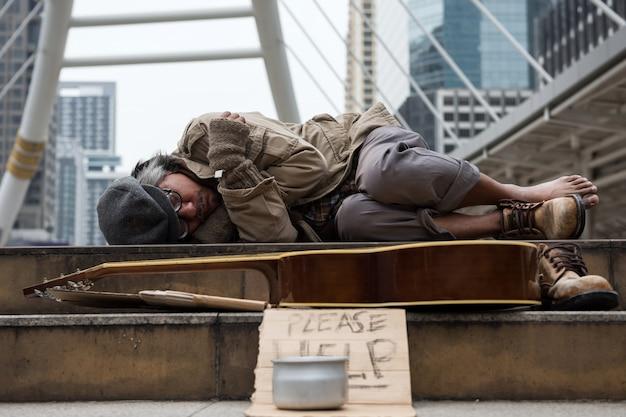 Oude dakloze man met slecht weer in de stad