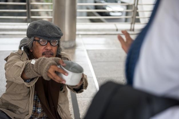Oude dakloze man vraagt om geld, maar weigert