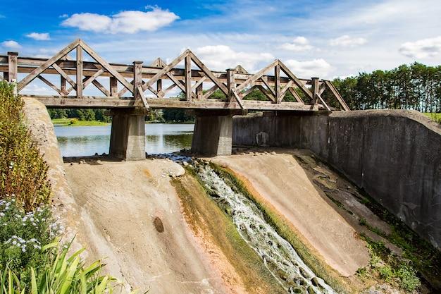 Oude dam met een houten brug. uitzicht op het zomerse zonnige landschap.