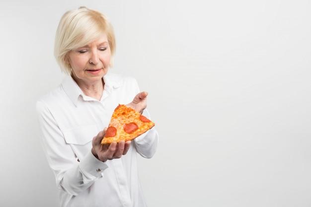 Oude dame die een groot stuk pizza in haar handen houdt. ze probeert te raden welke ingrediënten erin zitten. ook denkt ze erover om dat stuk te eten.