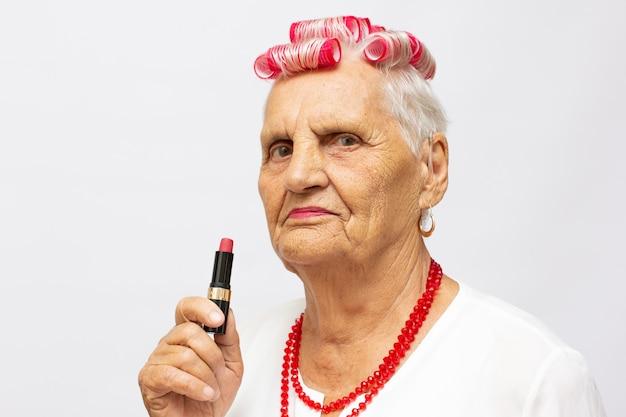 Oude dame die lippenstift op grijze achtergrond aanbrengt