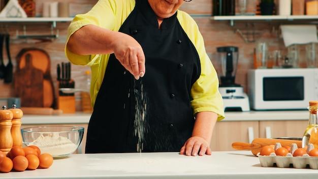 Oude dame die voedsel bereidt in de huiskeuken die bloem verspreidt voor het bakken van een recept. gepensioneerde bejaarde chef-kok met uniform besprenkelen zeven zeven ingrediënten met de hand op tafel koken zelfgemaakte pizza brood