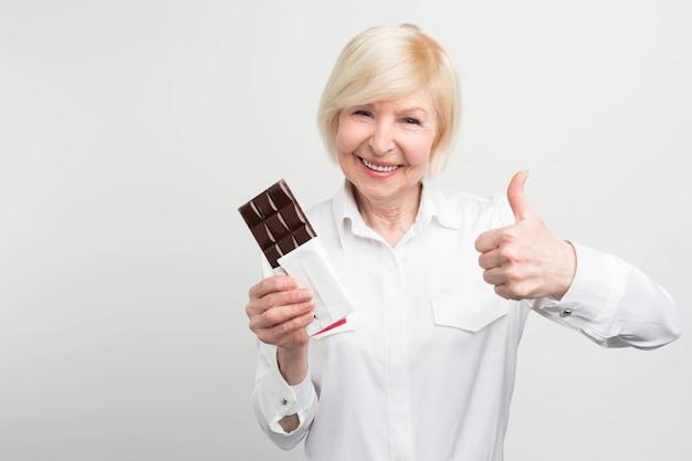 Oude dame houdt een reep goede chocolade en kijkt recht vooruit. ze vond het lekker. ze zou deze chocolade als de beste kunnen aanbevelen.