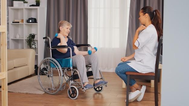 Oude dame in rolstoel die fysieke revalidatie doet met verpleegster. trainen, sporten, recupereren en tillen, bejaardentehuis, zorgverpleging, gezondheidsondersteuning, sociale hulpverlening, arts en ho